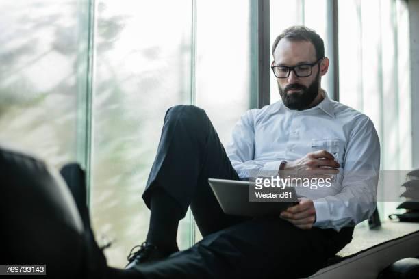 Businessman sitting by window, using digital tablet