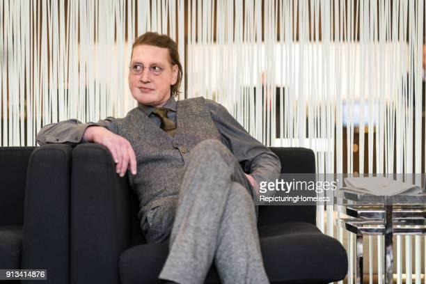 Ein Geschäftsmann sitzt lässig in der Hotellobby, lehnt sich an und schaut nach Rechts