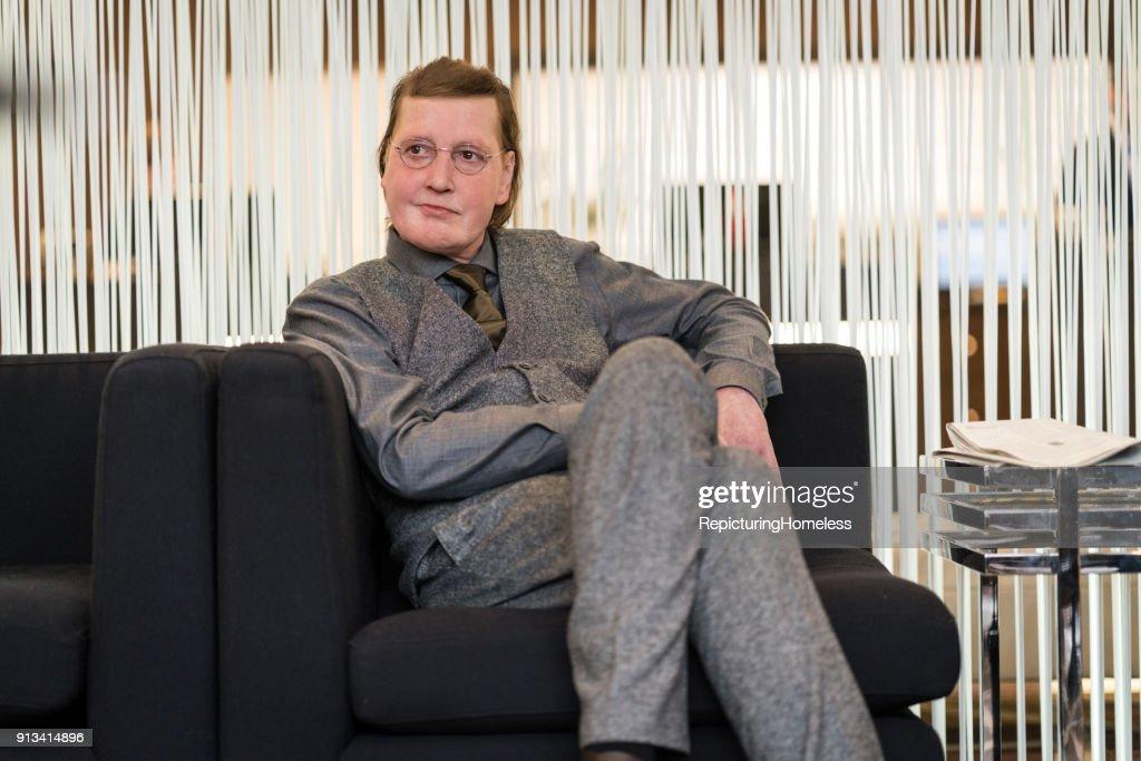 Ein Geschäftsmann sitzt lässig in der Hotellobby, lehnt sich an und schaut ins Leere : Stock-Foto