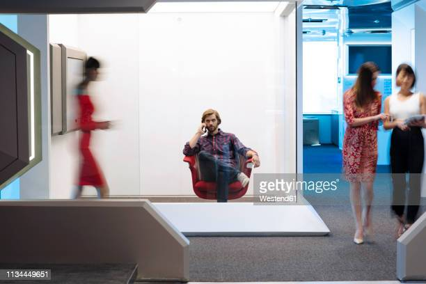 businessman sitting chair on a busy office floor, working - hub stock pictures, royalty-free photos & images