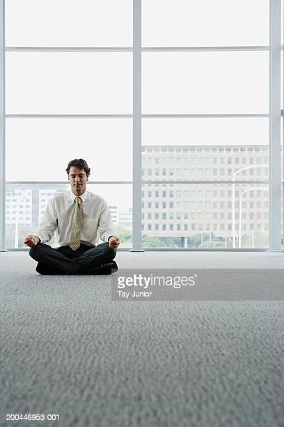 Businessman sitting cross-legged in office, meditating, eyes closed