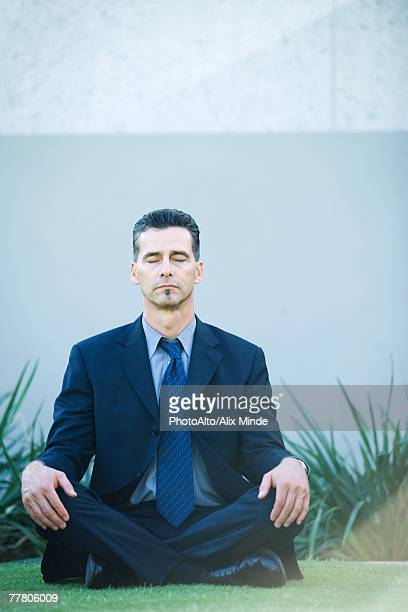 Businessman sitting cross-legged on grass, eyes closed