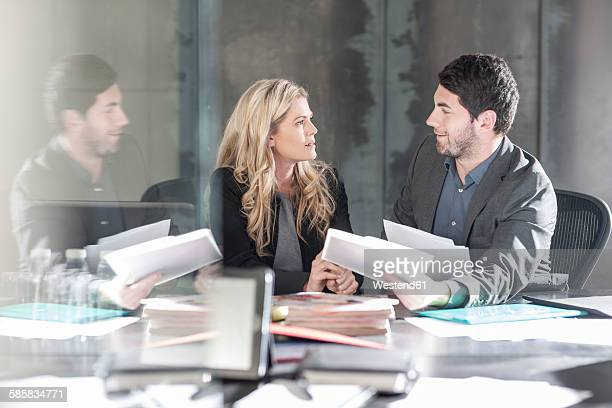 Businessman sitting face to face with woman at desk
