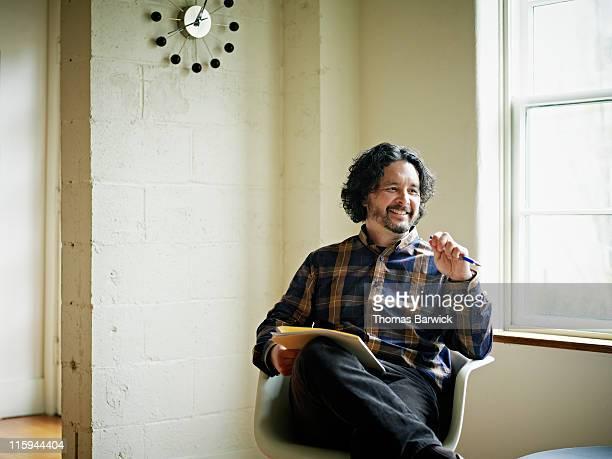 Businessman sitting holding folder smiling