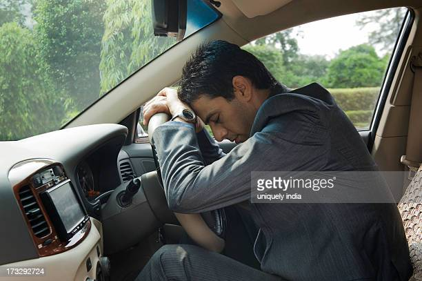 Businessman sitting in a car and looking upset