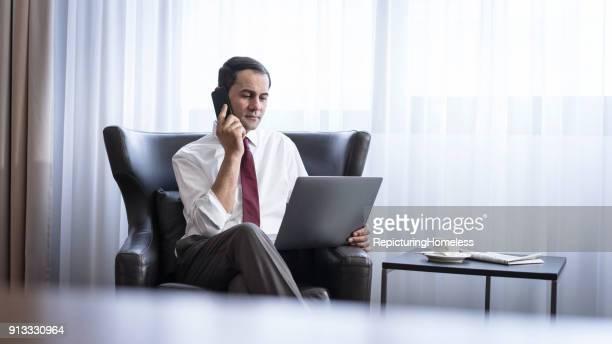 Ein Geschäftsmann sitzt in einem Sessel währrend er auf seinen Laptop schaut und telefoniert