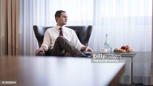 Ein Geschäftsmann sitzt in einem Sessel und schaut nach Rechts