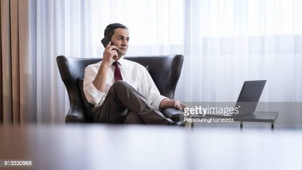 Ein Geschäftsmann sitzt in einem Sessel währrend er telefoniert