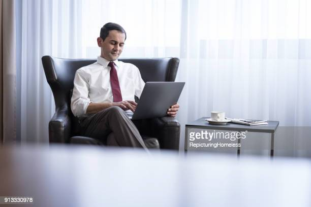 Ein Geschäftsmann sitzt in einem Sessel und arbeitet lächelnd an seinem Laptop
