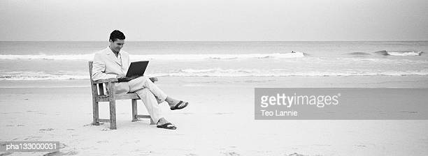 Businessman sitting in a chair on the beach with a laptop computer, B&W