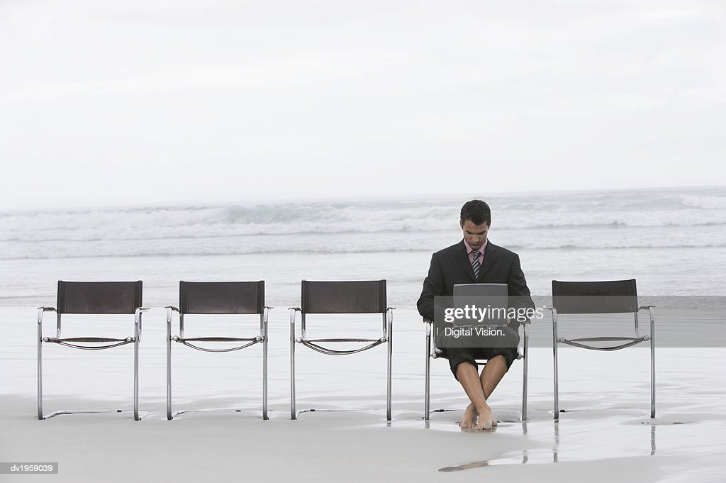Businessman Sitting in a Line of Chairs on a Beach Working on His Laptop : Stock Photo