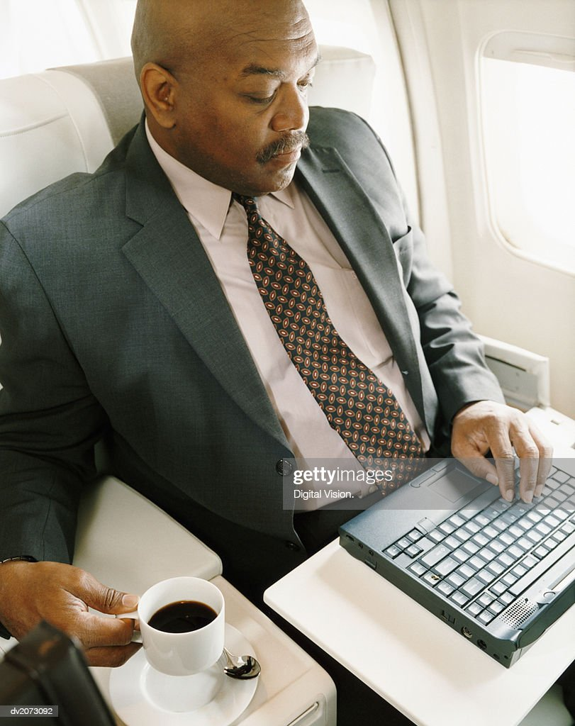 Businessman Sitting in a Seat in an Aircraft Using his Laptop : Stock Photo