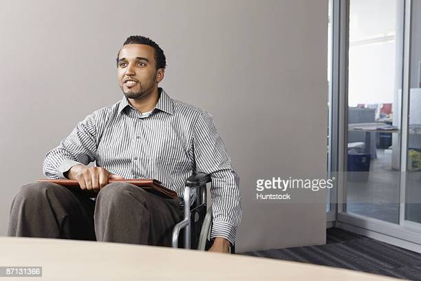 Businessman sitting in a wheelchair and smiling