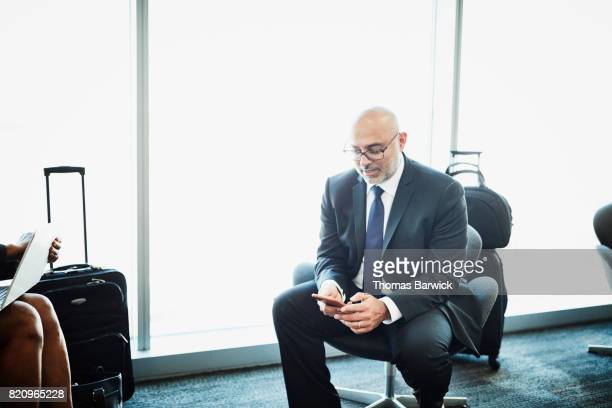 Businessman sitting in airport working on smartphone while waiting for flight