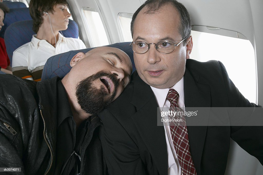 Businessman Sitting in an Aeroplane Trapped by a Man Sleeping by His Side : Stock Photo