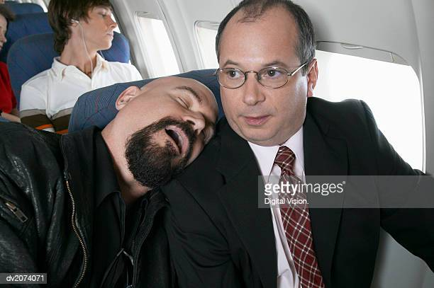 businessman sitting in an aeroplane trapped by a man sleeping by his side - uncomfortable stock pictures, royalty-free photos & images