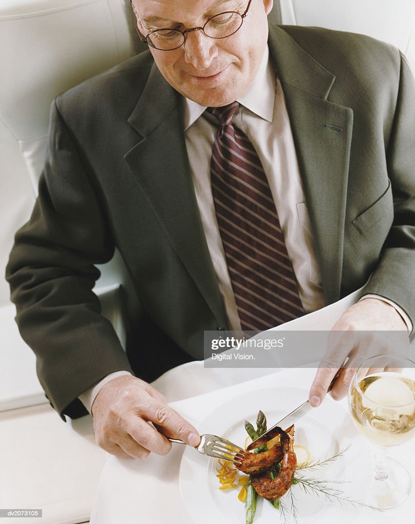 Businessman Sitting in an Aircraft Eating a Meal : Stock Photo