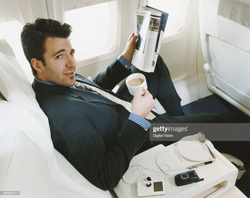 Businessman Sitting in an Aircraft Holding a Cup of Tea and Reading a Magazine : Stock Photo