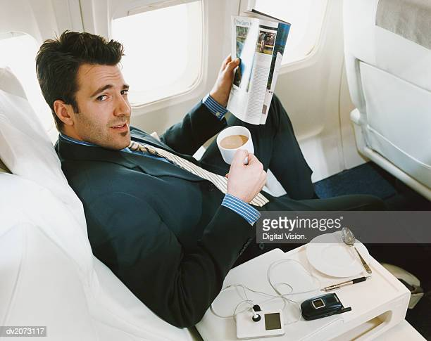 Businessman Sitting in an Aircraft Holding a Cup of Tea and Reading a Magazine