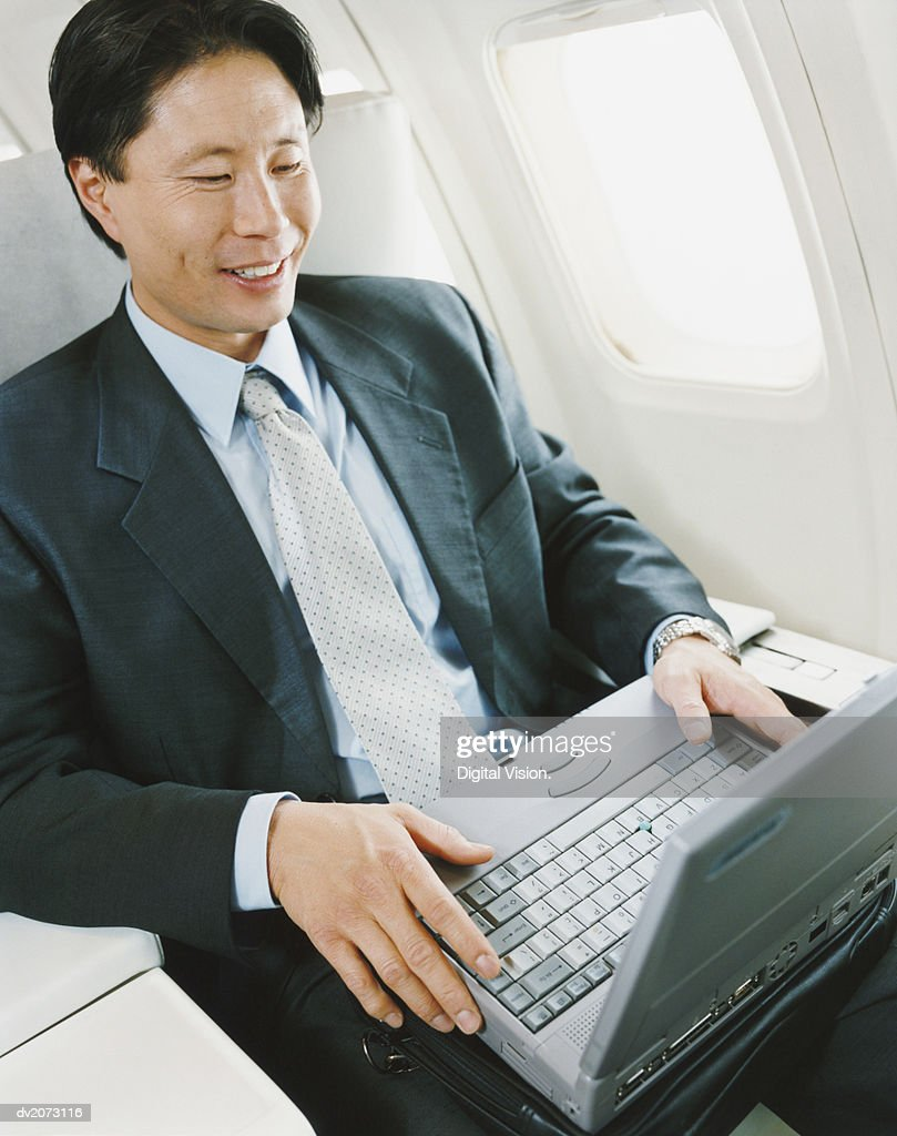 Businessman Sitting in an Aircraft Using a Laptop : Stock Photo