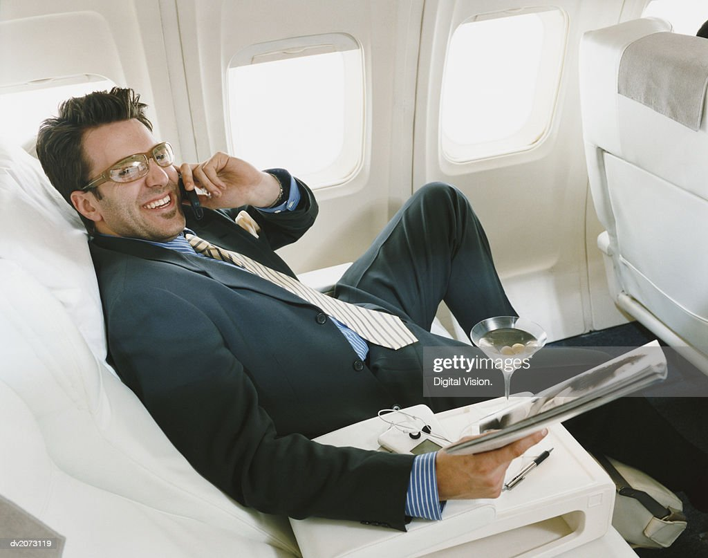 Businessman Sitting in an Aircraft Wearing Glasses and Holding a Magazine : Stock Photo