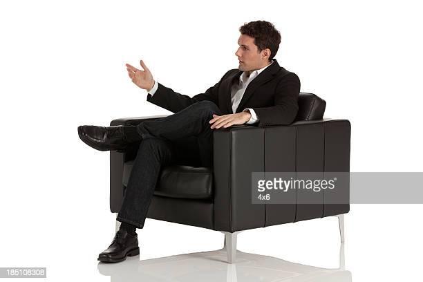 Geschäftsmann sitzt in einem amrchair