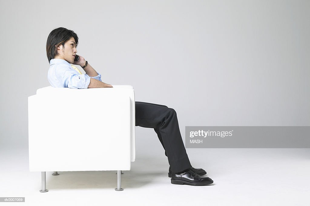 Businessman Sitting in an Armchair and Using a Mobile Phone : Stock Photo