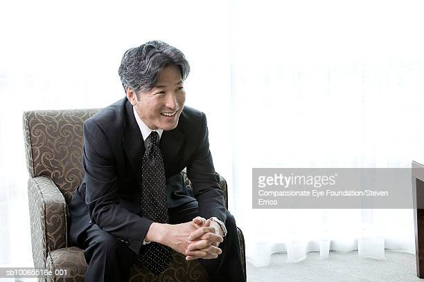businessman sitting in armchair and smiling - 身ぶり ストックフォトと画像