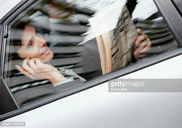 Businessman sitting in back of car, holding newspaper and cell phone, viewed through window