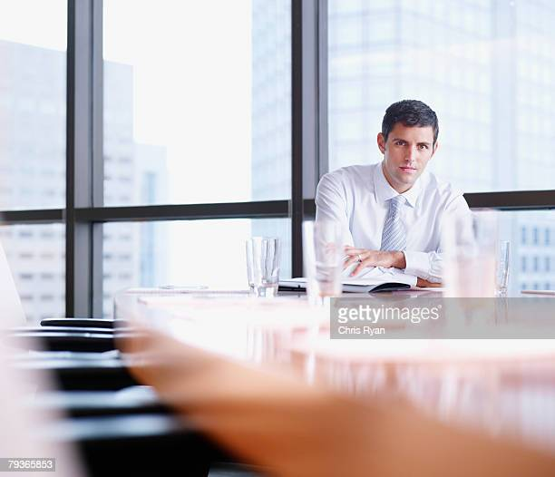 Businessman sitting in boardroom by large windows