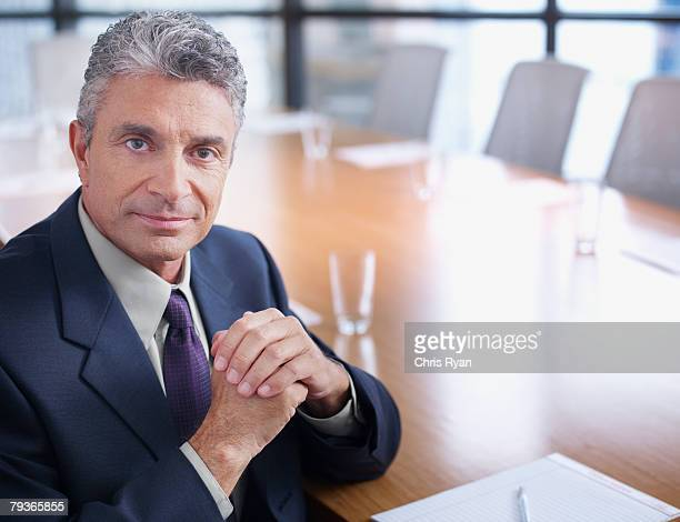 Businessman sitting in boardroom looking at camera