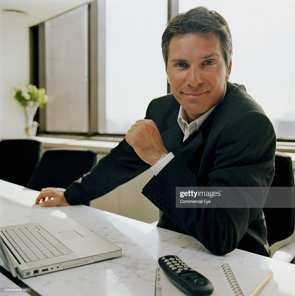Businessman sitting in boardroom with laptop and telephone, portrait : Stock Photo