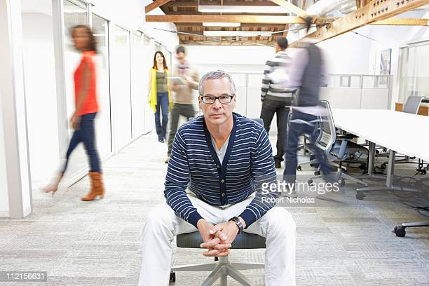 Businessman sitting in busy office