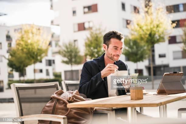 businessman sitting in cafe, drinking coffee, using smartphone - mann kaffee stock-fotos und bilder