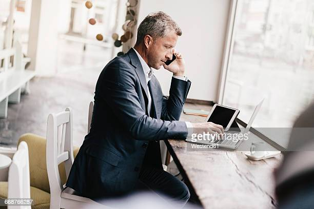 Businessman sitting in cafe, working