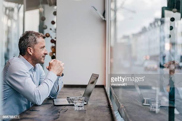 businessman sitting in cafe, working - foco diferencial imagens e fotografias de stock