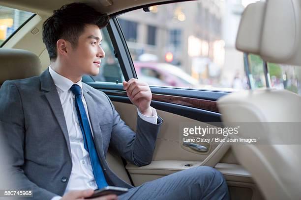 Businessman sitting in car back seat