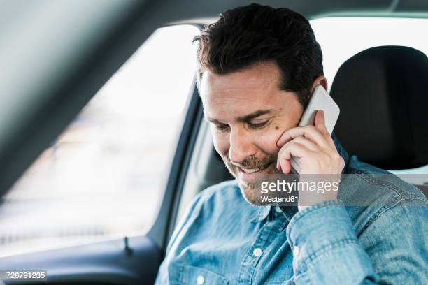 Businessman sitting in car talking on the phone