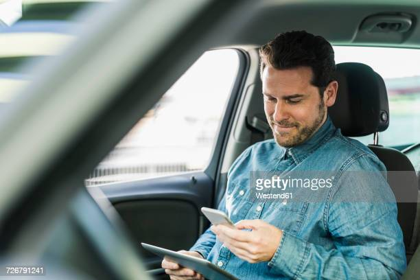 Businessman sitting in car using smartphone and digital tablet