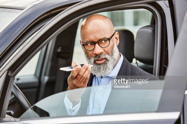 Businessman sitting in car using smartphone
