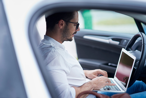 Businessman sitting in car working on laptop - gettyimageskorea