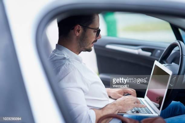 businessman sitting in car working on laptop - onafhankelijkheid stockfoto's en -beelden