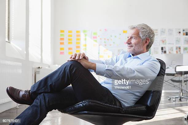 Businessman sitting in chair in office