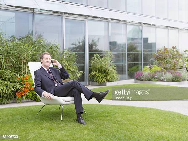 椅子に座っているビジネスマン芝生の上を使用して携帯電話 - 足を組む ストックフォトと画像