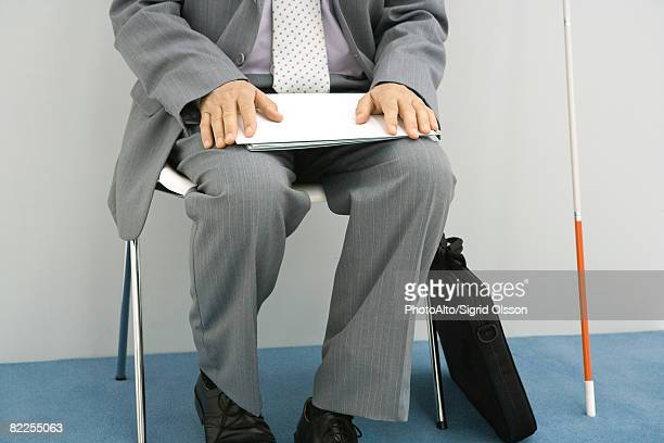 Businessman sitting in chair, white cane propped beside him, holding document, cropped
