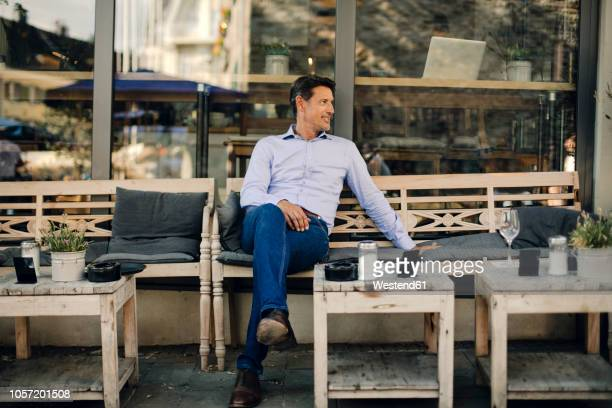 businessman sitting in coffee shop, smiling - bench stock pictures, royalty-free photos & images