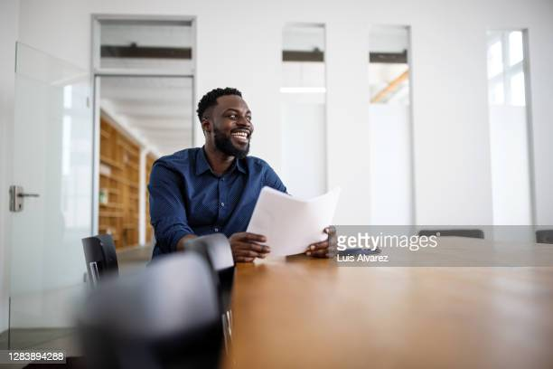 businessman sitting in conference room and smiling - lifestyle stock pictures, royalty-free photos & images