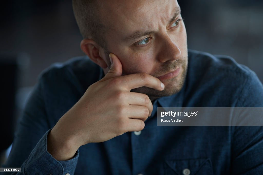 Businessman sitting in conference room, looking thoughtful : Stock Photo