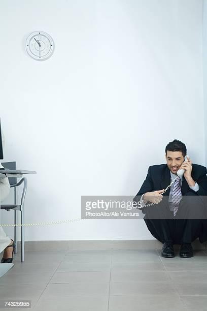 Businessman sitting in corner, talking on telephone