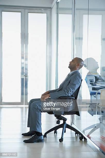 businessman sitting in corridor - oliver eltinger stock-fotos und bilder